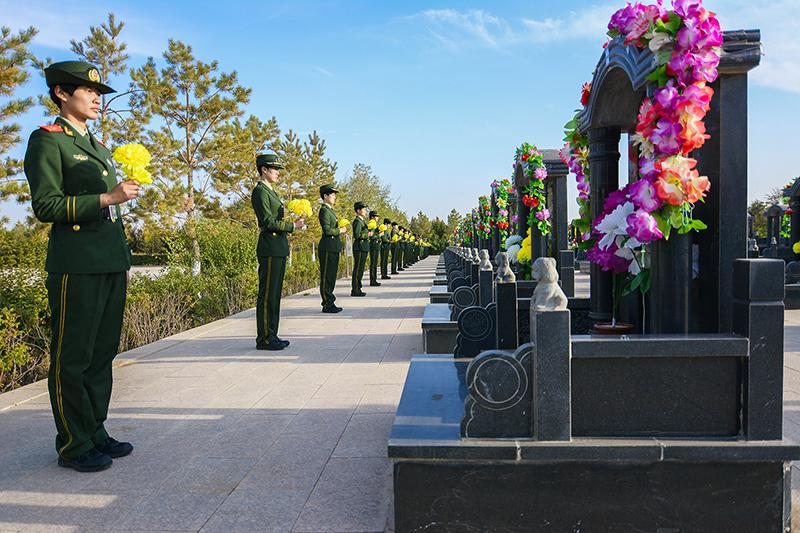 图为训练基地官兵在烈士墓碑前献花 闫宏伟摄